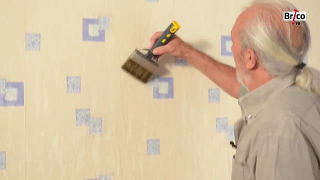 A l'aide d'un pinceau, on imbibe le papier peint avec de l'eau et du produit pour décoller du papier peint