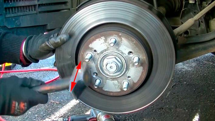 On tape sur le disque de frein avec le marteau